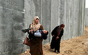 A Palestinian woman carries her son as she walks together in the mud   along the  8-meter-tall wall Israel is building to separate the outskirts of Jerusalem from the West Bank in the village of Abu Dis Thursday Jan. 15, 2004. Ahead of hearings next month at a world court on the legality of the massive barrier under construction, Israelis and Palestinians are bringing in high-profile foreign legal advisers and media specialists. Israel says is meant to keep out Palestinian suicide bombers and other attackers(Photo by Heidi Levine/Sipa Press).