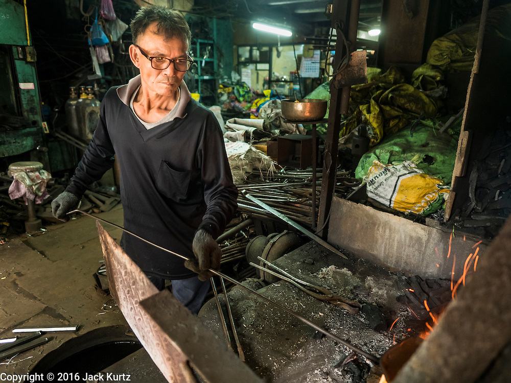 25 JANUARY 2016 - BANGKOK, THAILAND: A man checks metal in the furnace in a small one person workshop that makes heavy chains for boat anchors in Talat Noi, Bangkok. The metal for the chains is heated until it glows red and then it's pounded into shape. The Talat Noi neighborhood in Bangkok started as a blacksmith's quarter. As cars and buses replaced horse and buggy, the blacksmiths became mechanics and now the area is lined with car mechanics' and blacksmiths' shops.           PHOTO BY JACK KURTZ