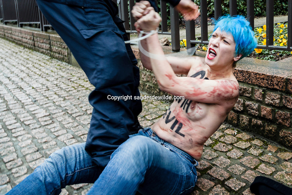 Naked female activist with blue hair of the Ukrainian movement Femen gets arrested while protesting in front of the European Council building shouting Russia's President Putin is the Apocalypse, during the EU-Russia summit, in Brussels, Friday, Dec. 21, 2012.
