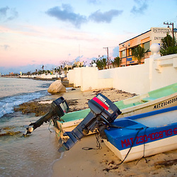 Several fishermans boats are lined up on shore in downtown Cozumel, Mexico as the sun sets on another warm winter day on this tropical island.