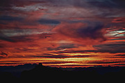 Winter desert sunset photo by Leandra Melgreen Lewis taken on the  Sky Island road to Mt. Lemmon in Tucson AZ. Sky is covered with red, gray and black billowing clouds over the area
