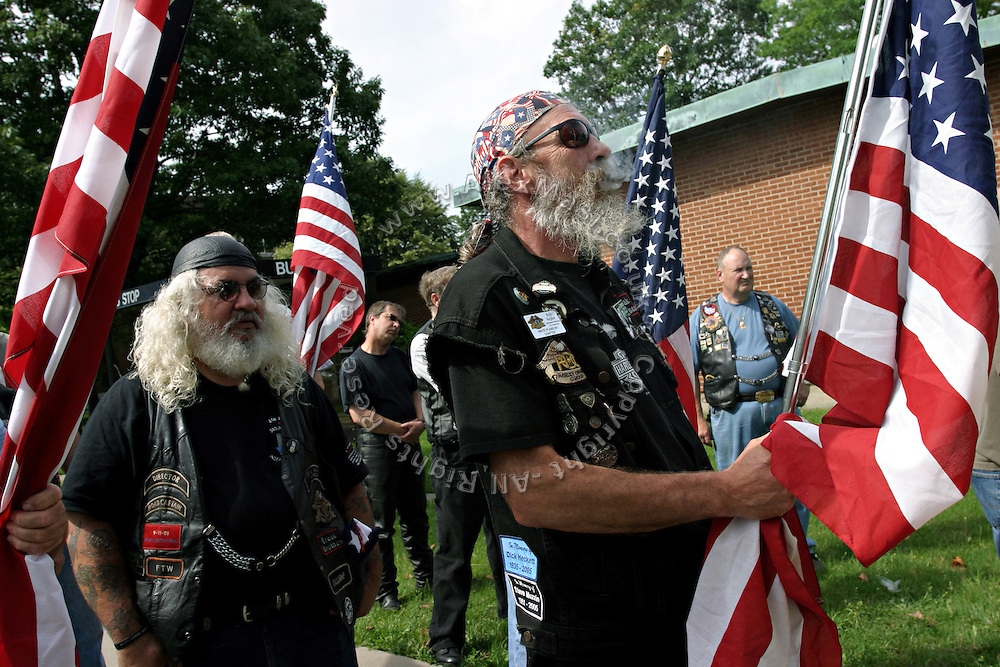 Members of the Patriot Guard Riders holding US flags while walking toward the church where the funeral service of Sgt. Ian T. Sanchez is scheduled, in Staten Island, NY., on Tuesday, June 27, 2006. Sgt. Sanchez, a 26-year-old American serviceman was killed by a roadside bomb in the Pech River Valley, Afghanistan. The Patriot Guard Riders is a diverse amalgamation of riders from across the United States of America. Besides a passion for motorcycling, they all have in common an unwavering respect for those who risk their lives for the country's freedom and security. They are an American patriotic group, mainly but not only, composed by veterans from all over the United States. They work in unison, calling upon tens of different motorcycle groups, connected by an internet-based web where each of them can find out where and when a 'Mission' is called upon, and have the chance to take part. This way, the Patriot Guard Riders can cover the whole of the United States without having to ride from town to town but, by organising into different State Groups, each with its own State Captain, they are still able to maintain strictly firm guidelines, and to honour the same basic principles that moves the group from the its inception. The main aim of the Patriot Guard Riders is to attend the funeral services of fallen American servicemen, defined as 'Heroes' by the group,  as invited guests of the family. These so-called 'Missions' they undertake have two basic objectives in particular: to show their sincere respect for the US 'Fallen Heroes', their families, and their communities, and to shield the mourners from interruptions created by any group of protestors. Additionally the Patriot Guard Riders provide support to the veteran community and their families, in collaboration with the other veteran service organizations already working in the field.   **ITALY OUT**