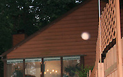 A beautiful pink orb floating over pool fence between house and photographer at dusk.