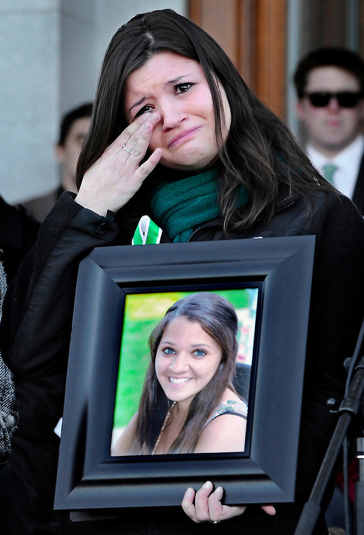 Heather Cronk, holds a photograph of her cousin of Sandy Hook Elementary School shooting victim teacher Victoria Soto,  as she wipes her eye during a rally at the Capitol in Hartford, Conn., Thursday, Feb. 14, 2013. Thousands of people turned out to call on lawmakers to toughen gun laws in light of the December elementary school shooting in Newtown that left 26 students and educators dead. (AP Photo/Jessica Hill)