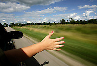 A young woman sticks her hand out of a traveling car during a road trip in Elgin Ontario on July 28, 2008.  Photo by Matthew Healey