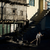 A street sweeper cleans the street on an early morning in Kargil