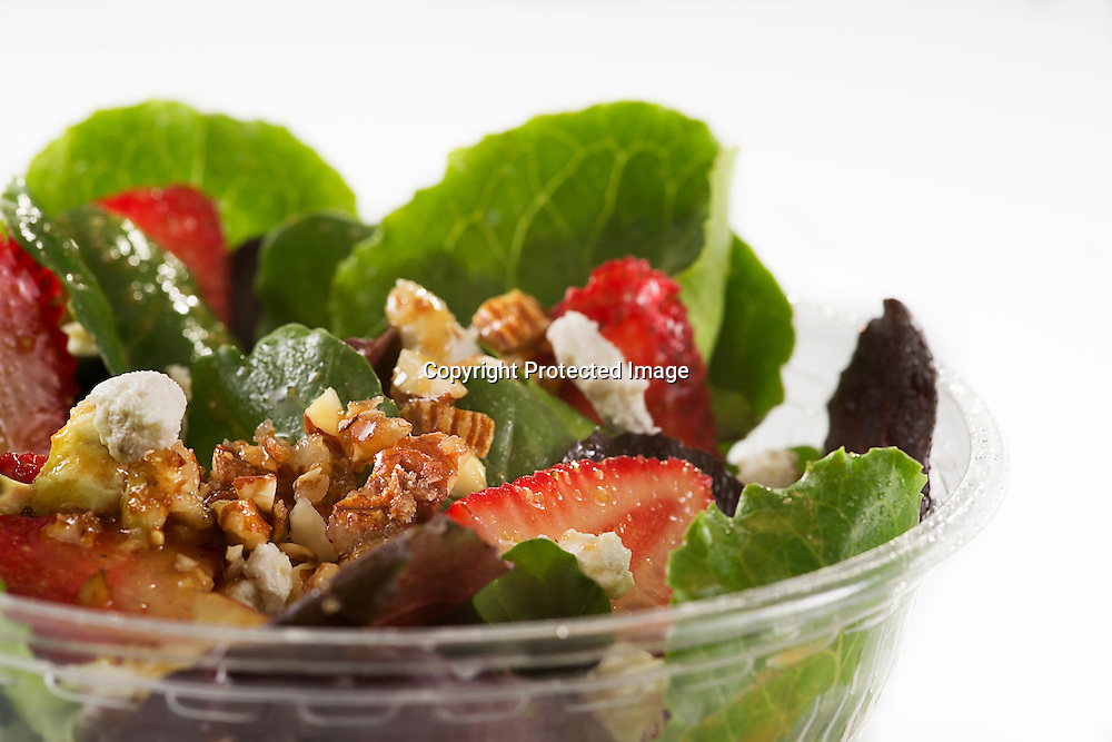 Red fruits salad with cranberry and strawberry, feta cheese, caramelized pecans and vinaigrette dressing.
