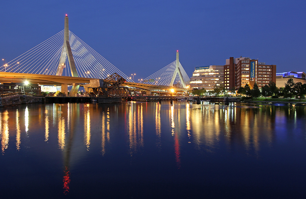 The Leonard P. Zakim Bunker Hill Memorial Bridge is a cable-stayed bridge across the Charles River in Boston, Massachusetts. This photography image shows the Zakim Bridge, Spaulding Rehabilitation Hospital, TD Bank North Garden, North Station, and their reflections at twilight as seen from the Paul Revere Park in Boston. Leonard Zakim was a civil rights leader. The Zakim bridge  was built as part of the Boston's Big Dig and it represents the worlds widest cable-stayed bridge.<br /> <br /> Pictures of Boston are available as museum quality photography prints, canvas prints, acrylic prints or metal prints. Prints may be framed and matted to the individual liking and decorating needs: <br /> <br /> http://juergen-roth.artistwebsites.com/featured/zakim-bridge-in-boston-juergen-roth.html<br /> <br /> Good light and happy photo making!<br /> <br /> My best,<br /> <br /> Juergen<br /> Prints: http://www.rothgalleries.com<br /> Photo Blog: http://whereintheworldisjuergen.blogspot.com<br /> Twitter: @NatureFineArt<br /> Facebook: https://www.facebook.com/naturefineart