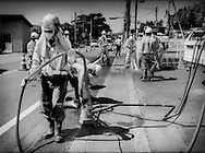 """Decontamination work crew on the main highway, that links highly radioactive Iitate-mura with Fukushima City and the sea, after the March 2011 meltdown at Fukushima Daiichi Nuclear Power Plant.  Local residents lament that the coastal strip of Fukushima Prefecture was known as the """"Ginza"""" of electric power plants because like the luxury shops lining Tokyo's Ginza District, power plants line the coast providing Tokyo consumers with power without any risk if things like this go wrong.  Residents may return to Iitate-mura but, due to the radioactive fall out from Fukushima Daiichi Nuclear Power Plant, the levels of radiation make it too dangerous to inhabit full time.  Iitate-mura, Fukushima Prefecture, Japan."""