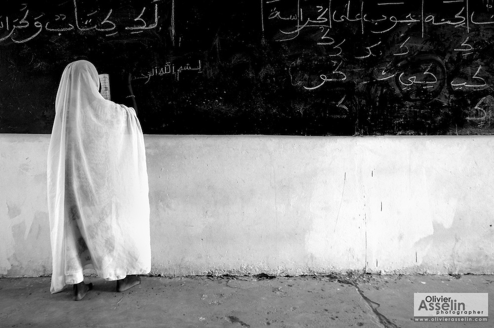 Girl writing on black board at the Mame Diarra Bousso koranic school in the village of Porokhane, Senegal, on Monday June 18, 2007.