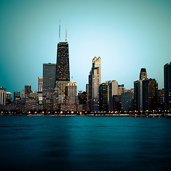 Photo of Chicago skyline at night time. Includes The John Hancock Center building which is one of the world's tallest skyscrapers and is a famous fixture in the Chicago skyline. Image is high resolution and toned green.