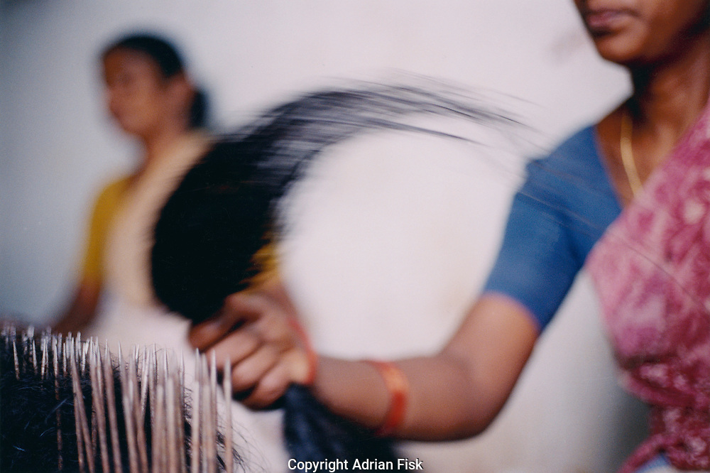 In a basement in Delhi a women repeatedly throws  cleaned village hair onto spikes whilst at the same time pulling it towards her. This ensures that all the hair left in her hand will be the same length.