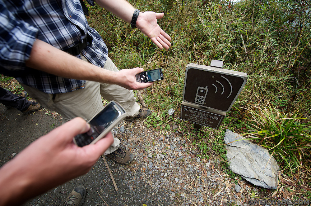 Hikers attempt to get a cell phone signal on a remote hiking trail deep in the mountains of central Taiwan.