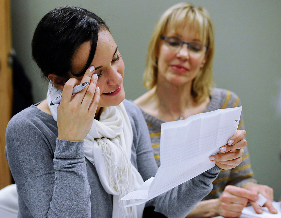 In this Friday, Feb. 22, 2013 photo, Stephanie Porzio, left, reads a condolence letter sent to Newtown alongside her mother Lauren Porzio, right, as they volunteer at the Newtown Volunteer Task Force in Newtown, Conn.  Volunteers are creating an archive of all the condolences and letters of support that arrived after December's massacre at Sandy Hook Elementary School, while other volunteers are saying thank you, one handwritten note at a time. Town officials estimate they received more than 175,000 letters and cards from around the world, many containing artwork or the thoughts of school children. (AP Photo/Jessica Hill)