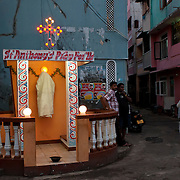 On Good Friday evening, a Muslim gentleman on his way home, walking past a  roadside shrine to St. Anthony. 2012