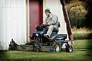 A farmer mows the lawn near his machine shed, Birch Hills, SK.