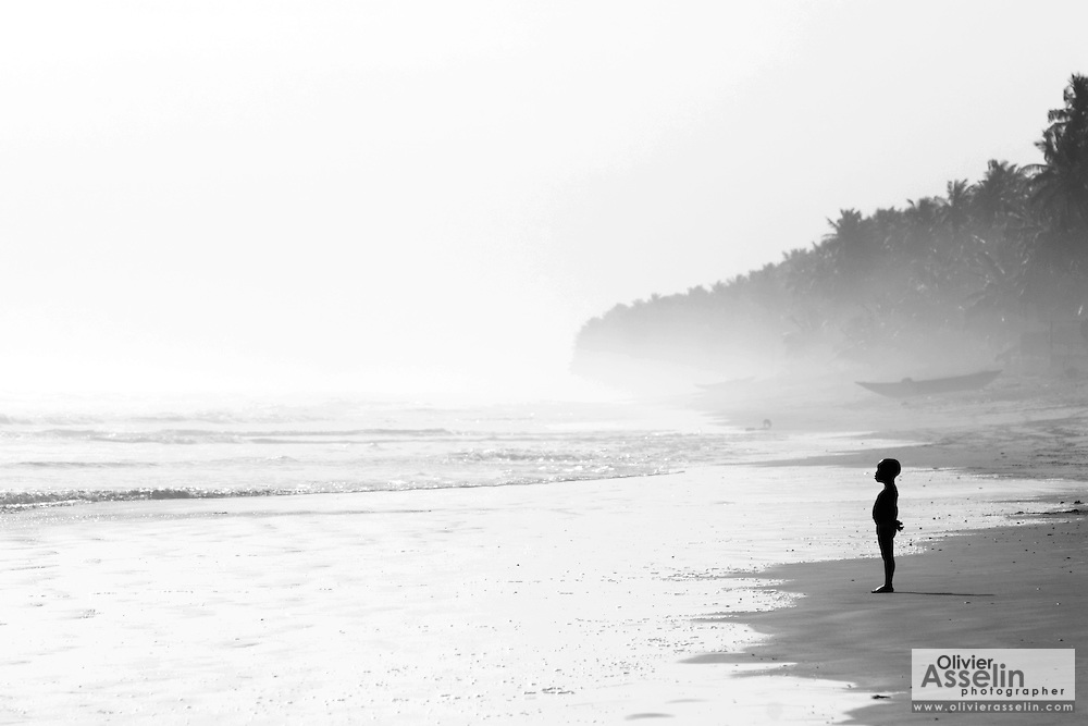 A young boy stands lonely on a hazy beach at Beyin, Western Ghana. ©Olivier Asselin, 2005