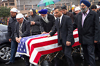Lodi, California: Mourners attend the flag-draped coffin of Parminder Singh Shergill, a US Army veteran of the first Gulf War who was shot by police near his home. Officers claim Shergill, who suffered from post-traumatic stress disorder, lunged at them with a knife; witnesses dispute the police account. He was buried with military honors.