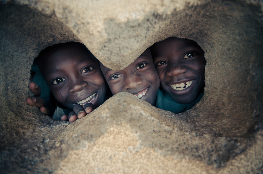 Happy students smile through a the holes in their classroom wall.