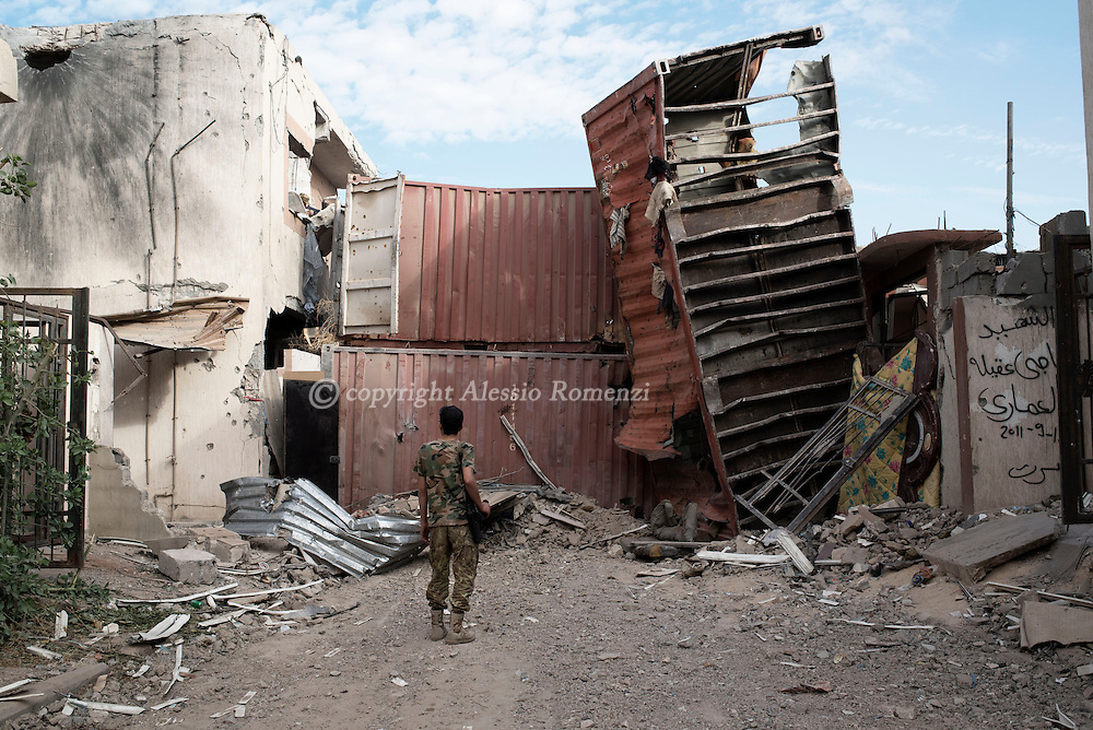 Libya, Sirte: A fighter of the Libyan forces affiliated to the Tripoli government looks at the barricade built with containers on the frontline with ISIS in Sirte on November 24, 2016.  Alessio Romenzi