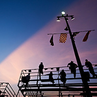 USA, Mississippi, Gulfport, Silhouette of stock car racing fans in bleachers with setting sun light at South Mississippi Speedway