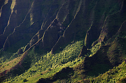 The knife-edged spines of cliffs in Kalalau Valley bask in sunlight at sunset in Na Pali Coast State Wilderness Park. Continious erosion of the volcano that created Kauai has produced the razor-thin cliffs that are the signature of the Na Pali coast. The view is from the Kalalau Lookout in Kokee State Park on the island of Kauai in Hawaii.