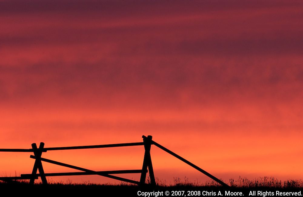 A rail fence is outlined by the orange hues at sunset at the Pawnee Buttes National Grasslands in northeastern  Colorado.