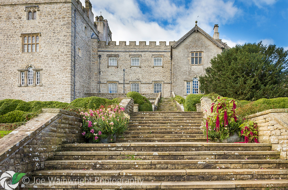 Brightened by pots of antirrhinums and Amaranthus caudatus, steps rise from the garden to the medieval Sizergh Castle, Cumbria.