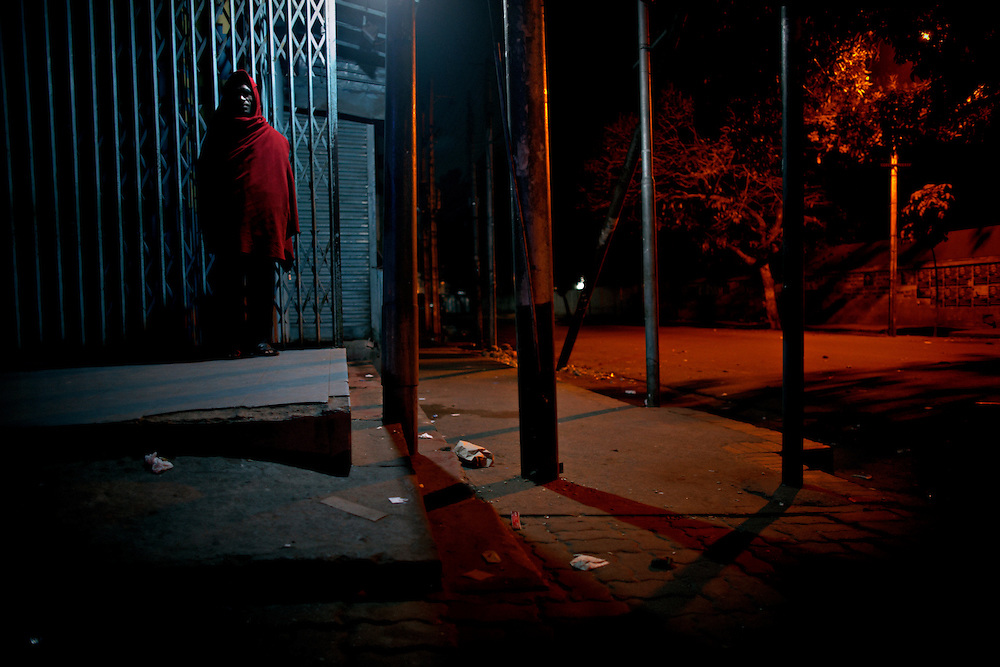 Man in red, Dhanmondi, Bangladesh...A man is guarding the street-corner and area surrounding shops...Bangladesh has finished with two years of emergency rule. The election results is compared to the landslide of 1970 that led to war and independence from Pakistan. .When preparations for the election started in late 2006, violent street-protests started, and led to a military backed interim government until the election happened under heavy security and watchful eyes on December 29th 2008...The past two years have seen a decrease of crime and corruption but also sparked violent student protests and curfews. Today  most people seem to be happy to return to some sort of normality. But in one of the poorest countries in the world where 80% live for less than a dollar a day, does it really matter who is in power? The circus is over, back to reality and putting food on the table...A blogger  from dhaka is quoted Ó we prefer messy democracy to military ruleÓ...Is this the end of night, a new dawn or yet another dusk?..Photo by: Eivind H. Natvig/MOMENT *** Local Caption ***