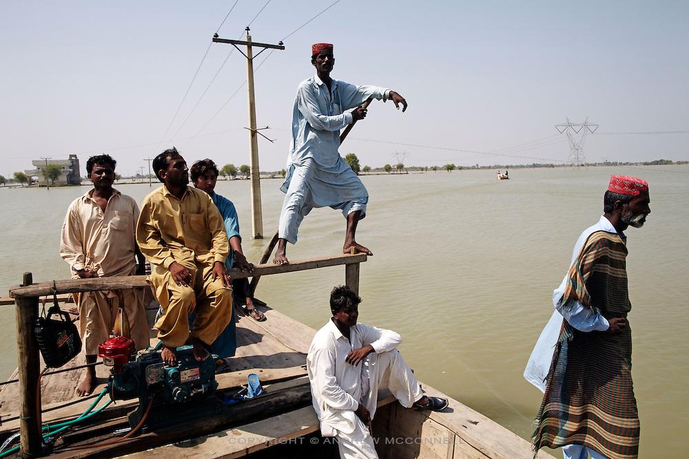 People are ferried across flood water, near Ghauspur, in Sindh Province, Pakistan.