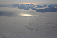 Aerial view of mountains and fjords covered in snow and ice in April in Isfjorden on flight from Longyearbyen to Ny-Alesund; Svalbard, Norway.