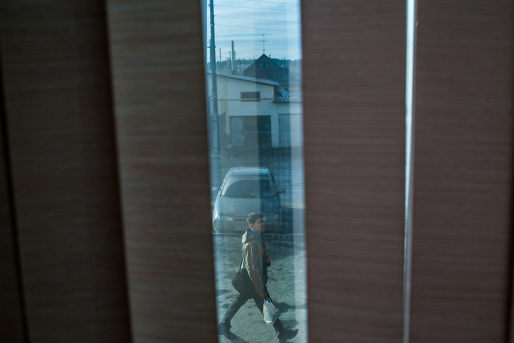 A man walks down the street, as seen from inside a restaurant, on Wednesday, November 13, 2013 in Asbest, Russia.