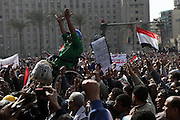 """A man in a wheel chair is lifted into the air as  anti government supporters attend a massive rally in  Tahrir Square in Cairo February 4, 2011. Thousands of Egyptians prayed in Cairo's Tahrir (Liberation) Square on Friday for an immediate end to Mubarak's 30-year rule, hoping a million more would join them in what they called the """"Day of Departure"""". Photo by Heidi Levine /Sipa Press"""