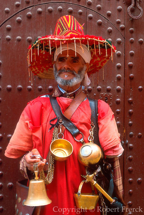 MOROCCO, MARRAKECH Medina; a water vendor with brass cups in traditional dress and hat