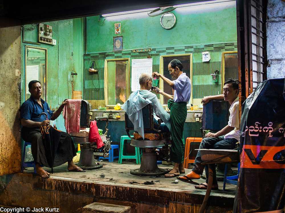 04 JUNE 2014 - YANGON, YANGON REGION, MYANMAR: A barbershop in Yangon, Myanmar. Yangon, with a population of over five million, continues to be the country's largest city and the most important commercial center.     PHOTO BY JACK KURTZ