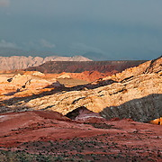 Sunset light illuminates colorful orange, pink, yellow, and white sandstone in White Domes area of Valley of Fire State Park, Nevada, USA. Starting more than 150 million years ago, great shifting sand dunes during the age of dinosaurs were compressed, uplifting, faulted, and eroded to form the park's fiery red sandstone formations. The park also boasts fascinating patterns in limestone, shale, and conglomerate rock. The park adjoins Lake Mead National Recreation Area at the Virgin River confluence, at an elevation of 2000 to 2600 feet (610-790 m), 50 miles (80 km) northeast of Las Vegas, USA. Park entry from Interstate 15 passes through the Moapa Indian Reservation. (Panorama stitched from 8 photos.)