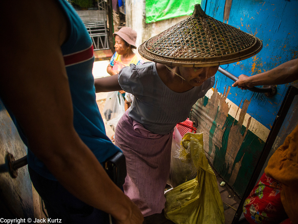 05 JUNE 2014 - YANGON, YANGON REGION, MYANMAR: A woman boards the Yangon Circular Train. The Yangon Circular Train is a commuter train that circles Yangon, Myanmar (Rangoon, Burma). The train is 45 kilometers long, makes 38 stops and takes about three hours to make a loop of the city.     PHOTO BY JACK KURTZ