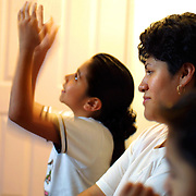 Veronica Gallegos (right) and her son Rey, Jr., (bottom) listen to her daughter Janet Lee speak of her father's death from leukemia and how the angels decended from heaven to take him away. He worked for 10 years at the former Viewmaster plant in Beaverton.