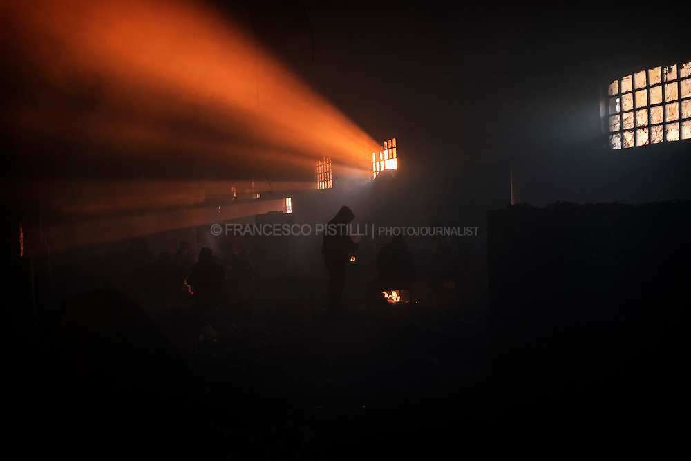 The dark smoke renders the visibility to only a few meters, but the darkness is pierced by the sounds of people coughing, choked by the smoke and the cold weather. Inside the warehouse where more than one thousand of Afghan and Pakistani migrants are living, the air is thick with smoke from several makeshift fires and groups of men huddle together trying to thaw their hands by the flames.
