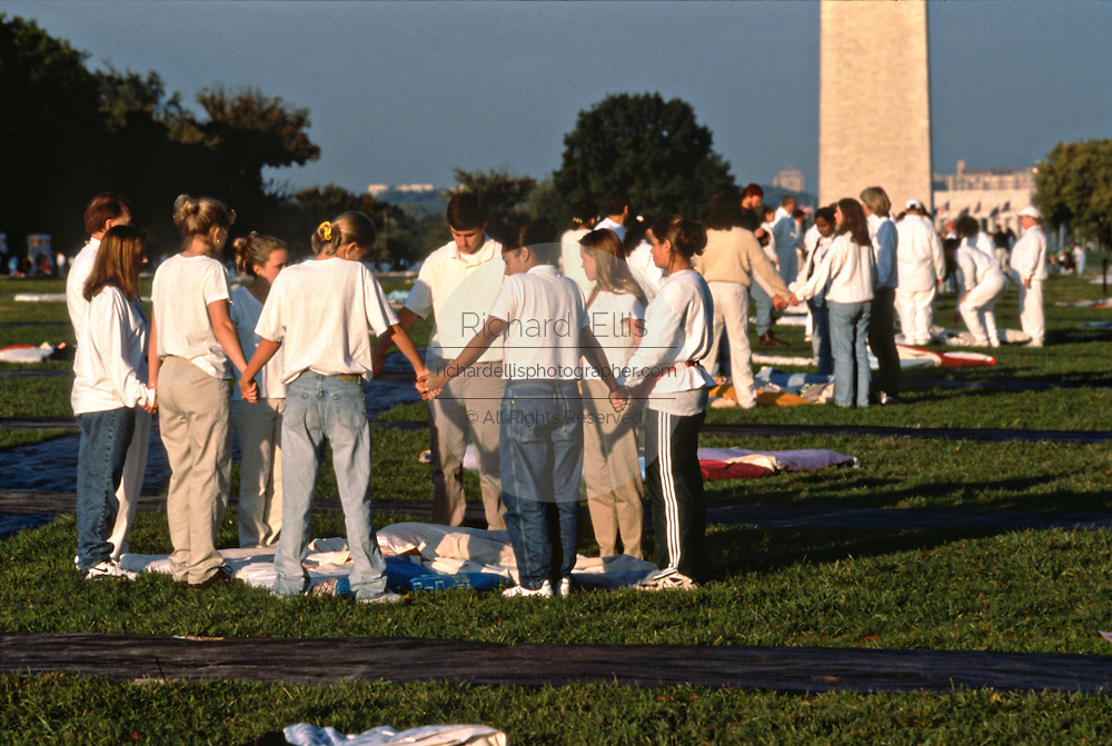 Volunteers hold a brief prayer before spreading the entire AIDS Memorial Quilt out along the National Mall October 11, 1996 in Washington, DC.