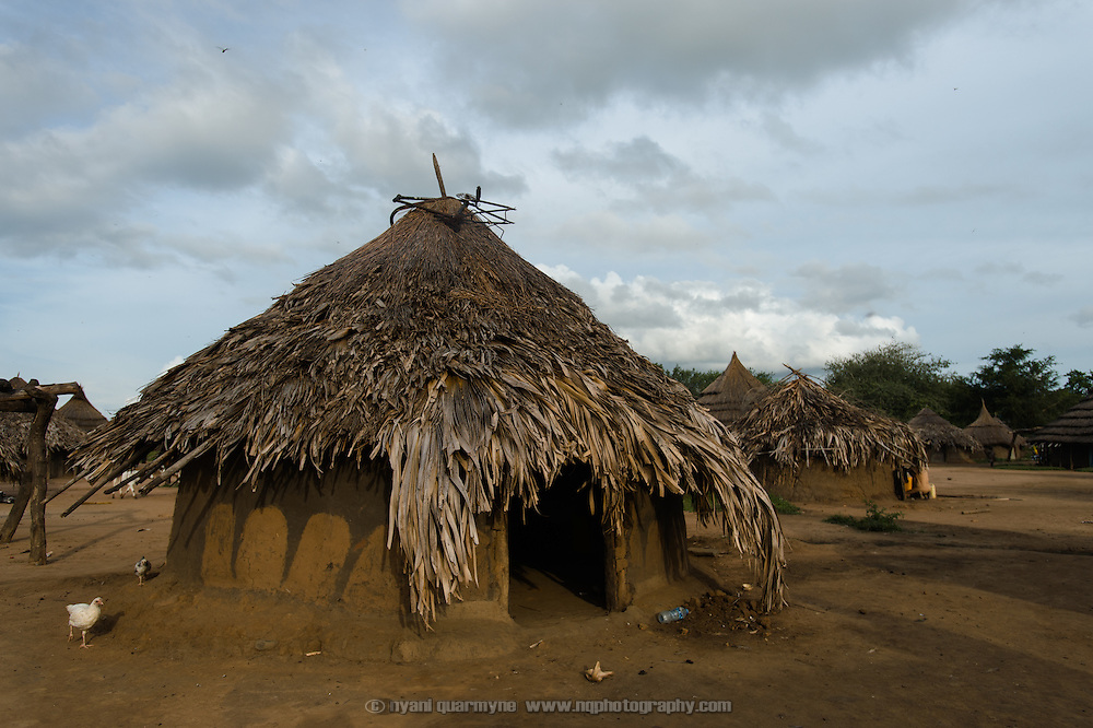 """Simon Jackson's home in the village of Kudo in Eastern Equatoria in South Sudan on 8 August 2014. Jackson says he was unable to farm this year due to illness—""""Alas, it has caused me problems""""—leaving himself and his wife and their eight children in a precarious position. Unemployed, he says, """"You find any opportunity out there, and you make small money and you buy food for the children. I hustle and I take any small, small jobs I can find. If wasn't sick, I would have been able to farm, and I would have food."""" At times, when he cannot find work, he is forced to borrow: """"I find somebody who had a good harvest and borrow from them. If I took a bowl, I return a bowl, if I took ten bowls I return 10 bowls."""" Simon received sorghum, vegetable and maize seeds to plant during a Plan International distribution. Asked what he will do with his future harvest, he replies, """"Why would anyone in their right mind eat everything? You eat some, and you keep some. I will do my best, and whatever God blesses us with we will use it, and we will keep some. But I have no guarantee."""""""