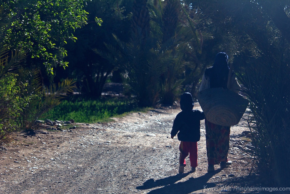 Africa, Morocco, Skoura. Moroccan mother and child walking on village road.