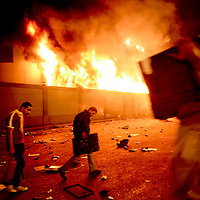 Looters take items as the National Democratic Party headquarters burns in downtown Cairo, Egypt. January 2011.