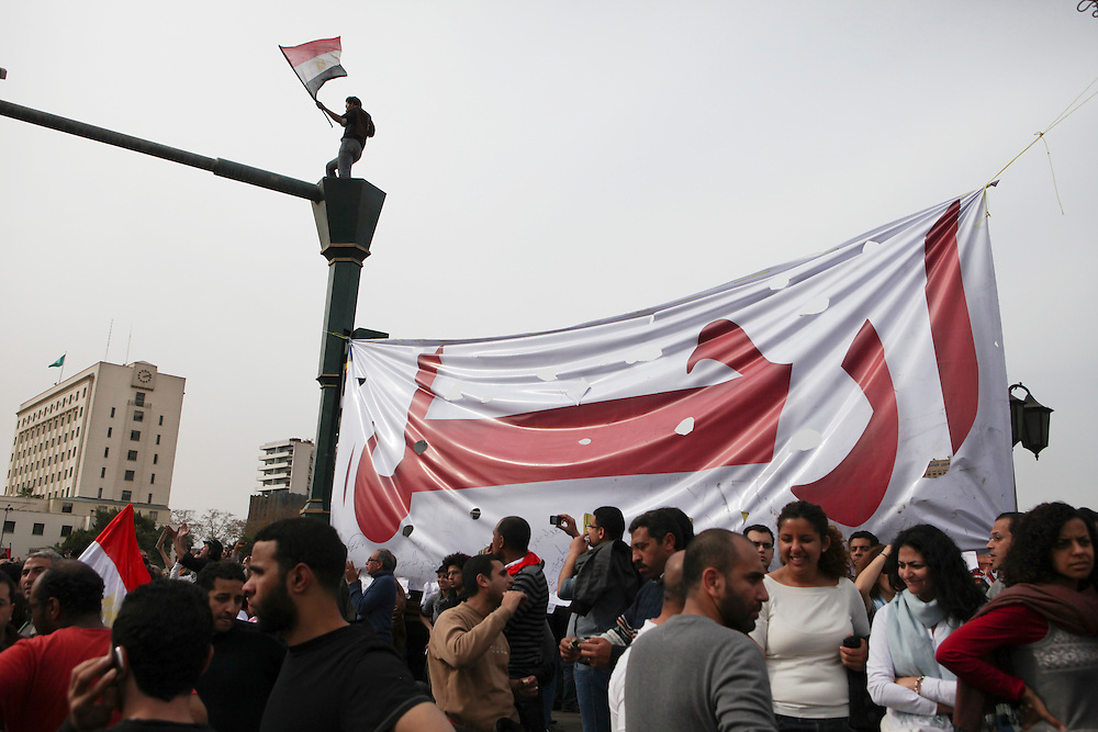 """Protesters at Tahrir Square calling for President Hosni Mubarak's ouster stand in front of a sign reading """"leave."""""""