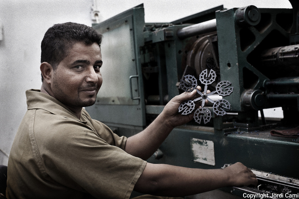 "A worker ""Zabbaleen"" sample injected plastic parts used in construction, produced from recycled plastic recycling plant Katameya, who heads the NGO APE on the outskirts of Cairo. In the middle of Manshiet Nasr a Cairo neighborhood is located Mokattam settlement known as ""Garbage City"" is inhabited by Zabbaleen, a community of about 45,000 Coptic Christians living for decades to recycle waste generated by the Egyptian capital: plastic, aluminum, paper and organic waste transformed into compost. Most part of the Association for the Protection of the Environment (APE), an NGO that works in the area, whose objectives are to protect the environment and improve the livelihoods of garbage scavengers in Cairo. According to the UN, the work is done in Mokattam is one of the ten best examples of world environmental improvement. El Cairo , Egipt, June 2011. ( Photo by  Jordi Camí )."