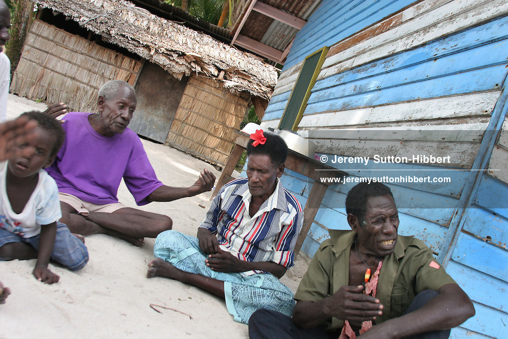 """Wise men"" of the ""council of elders"" sit discussing traditional prayers and secret ceremonies that they have performed to halt the erosion of their land by the sea, on Han Island, Carterets Atoll, Papua New Guinea, on Monday, Dec. 11, 2006.  Rising sea levels have eroded much of the coastlines of the low lying Carteret islands (situated 80km from Bougainville island, in the South Pacific), and waves have crashed over the islands flooding and destroying what little crop gardens the islanders have. Food is in short supply, banana and swamp taro crops are failing due to the salt contamination of the land, and the islanders live on a meagre one meal per day diet of fish and coconut. There is talk by the Autonomous Region of Bougainville government to relocate the Carteret Islanders to Bougainville island, but this plan is stalled due to a lack of finances, resources, land and coordination."