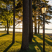 Lake Mitchell at sunset, lampposts at Lakeside Charlies restaurant, Cadillac, Michigan, USA.
