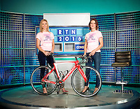 Rachel Riley and Susie Dent photographed on on the Countdown TV set in front of letters board. Susie Dent is wearing a woman against Cancer T Shirt and is leaning over a professional racing cycle
