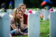 Marina Clifford, 12, a volunteer with Memorial Day Flowers, comforts US Armn Reservist Sgt. Heidi Heming, 27 of Chattanooga, TN, as she they sit in front of the headstone of US Army SPC Christopher J. Coffland in Arlington National Cemetery in Arlington Virginia, USA on 27 May, 2013. Heming and Coffland served together in Afghanistan.