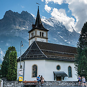 The Eiger rises behind a church across the street from Hotel Gletschergarten in Grindelwald, Switzerland, the Alps, Europe.